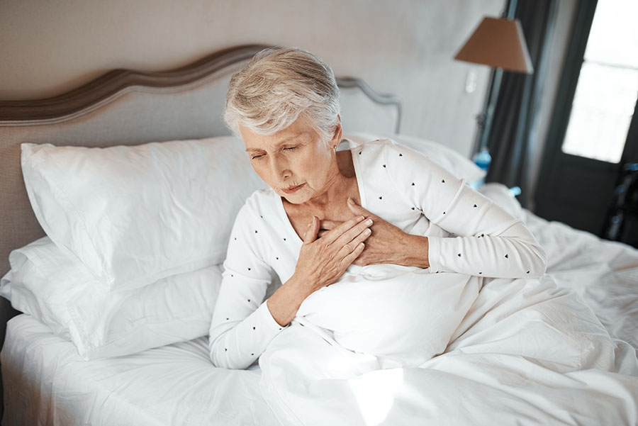 Woman in bed in pain holding her chest
